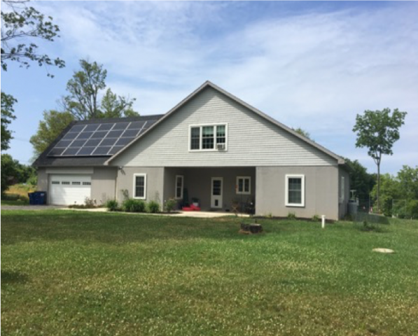 Image of geothermally heated home in Sterling, NY with solar panels on the roof