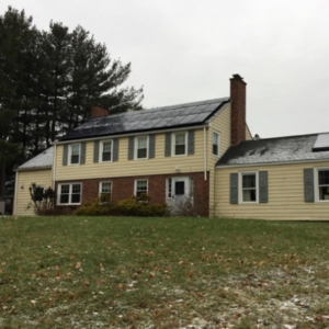 two story split house in winter with solar panels on roof
