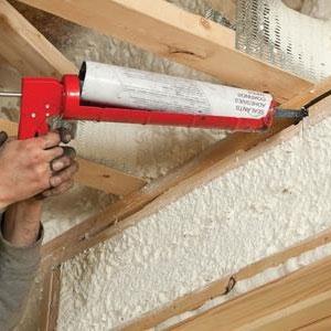 11a caulking gun sealing an attic above insulation