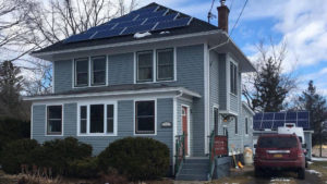 11A house with solar panels on the roof and in the back yard